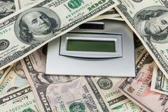 Hundert Dollar, der auf dem Taschenrechner liegt Stockbilder
