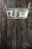 Hundert Dollar, die an der Wäscheleine hängen Stockbilder