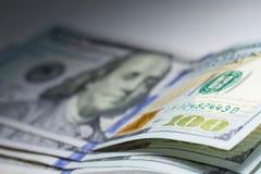Hundert Dollar schließen oben mit selektivem Fokus und Scheinwerferlicht Stockfoto