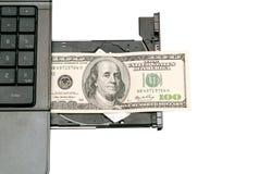 Hundert Dollar sind auf der CD-ROM des Computers Stockfotos
