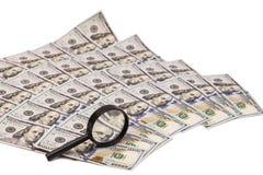 Hundert Dollarbanknoten unter Lupe Stockbilder