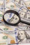 Hundert Dollarbanknoten unter Lupe Stockfotografie