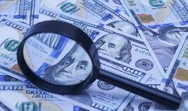 Hundert Dollarbanknoten unter Lupe Stockbild