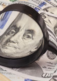 Hundert Dollarbanknoten unter Lupe Lizenzfreie Stockfotografie