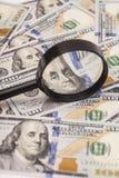 Hundert Dollarbanknoten unter Lupe Stockfoto