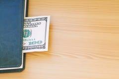 Hundert Dollarschein, der im Notizbuch liegt Stockfotografie