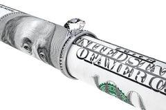 Hundert Dollarschein in einem Ring der diamantenen Hochzeit Stockfotografie
