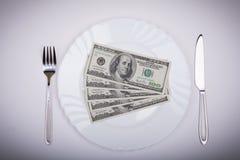 Hundert Dollarscheine auf Platte Stockfotos