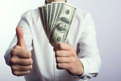 Hundert Dollarscheine in den Händen Stockbilder