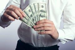 Hundert Dollarscheine in den Händen Lizenzfreie Stockbilder