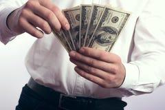 Hundert Dollarscheine in den Händen Stockfotografie