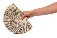 Hundert Dollarscheine in der weiblichen Hand, die gestapelt wurde, lockerten heraus lokalisiert auf Stockfotos