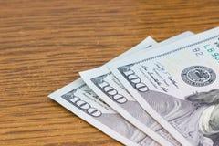 hundert Dollarscheine, die auf einem hölzernen liegen Stockbild