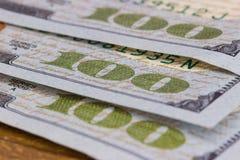hundert Dollarscheine, die auf einem hölzernen liegen Lizenzfreies Stockbild