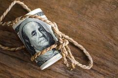 Hundert Dollarscheine oben gerollt mit Seil Lizenzfreie Stockfotografie