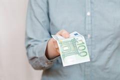 Hundert Eurobanknote im Arm Stockfotos