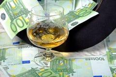 Hundert Eurobanknoten mit einem Glas des schwarzen Hutes des Kognaks Stockbilder
