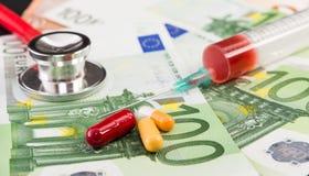 Hundert Eurorechnungen mit Pillen Spritze und Stethoskop lizenzfreies stockbild