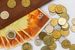 Hundert Schekelrechnungen umgeben durch viele Münzen auf einem weißen Hintergrund stockfotos