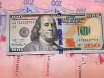 Hundert von Dollar und von grivnas Banknoten Stockbilder