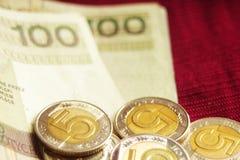 Hunderte vom polnischen Zloty zusammen mit fünf Zlotymünzen auf königlichem rotem Hintergrund stockfotos