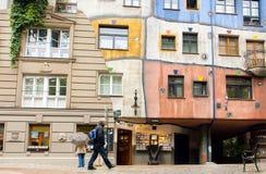 走在房子附近的游人建造用奥地利艺术家Hundertwasser的概念 免版税库存照片