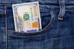 Hundra amerikanska dollar räkning i fack av jeans Arkivbild