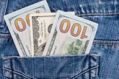 Hundra amerikanska dollar räkningar i fack av jeans Royaltyfri Bild