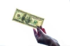 Hundra dollar i flickans hand Arkivfoton
