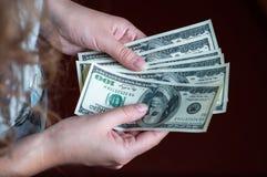 Hundra dollar i flickans hand Royaltyfri Foto