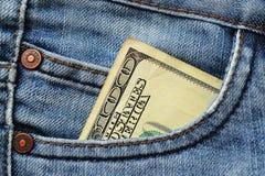 Hundra dollar räkning i facket av jeans stänger sig upp royaltyfria foton