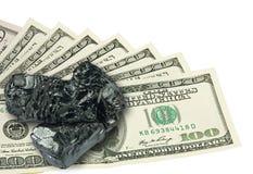 Hundra dollar sedel och rått kol överst Arkivbild