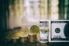 Hundra dollar sedlar av bunten av mynt från fjärdedelar och en dollar Royaltyfri Bild