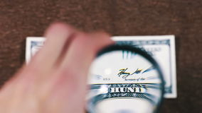 Hundra dollar under förstoringsglaset stock video