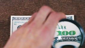 Hundra dollar under förstoringsglaset arkivfilmer