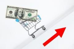 Hundra dollarräkning i vagn Stigning upp riktning med det röda piltecknet Tillväxt av rikedombegreppet Växande statsskuld arkivfoton