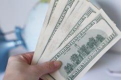 Hundra dollarräkningar i hand Den kvinnliga handen rymmer många dollar arkivbild