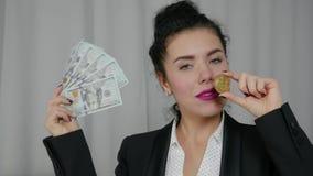 Hundra dollarräkningar och Bitcoin i händerna lager videofilmer