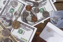 Hundra dollarräkningar och en dollar mynt på en träbakgrund Royaltyfri Fotografi
