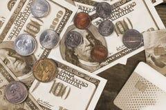 Hundra dollarräkningar och en dollar mynt på en träbakgrund Royaltyfri Foto