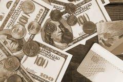 Hundra dollarräkningar och en dollar mynt på en träbakgrund Arkivfoton