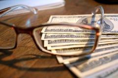 Hundra dollarräkningar och exponeringsglas på en tabell arkivfoto