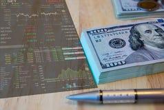 Hundra dollarräkningar och penna på den gamla trä och aktiemarknadpristabellen på beside Fotografering för Bildbyråer