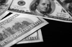 Hundra dollarräkningar på en mörk bakgrund som är svartvit Royaltyfria Foton
