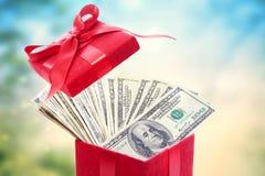Hundra dollarräkningar i en stor röd närvarande ask Arkivbild