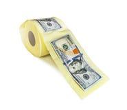 Hundra dollarräkningar på en rulle av toalettpapper Arkivbild