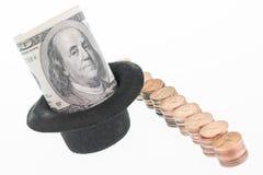 Hundra dollarsedel i en hatt och en rad av en encentmynt Arkivfoton
