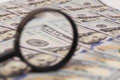 Hundra dollarsedel under förstoringsglaset Royaltyfri Bild