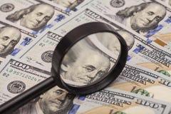 Hundra dollarsedel under förstoringsglaset Arkivbild