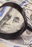 Hundra dollarsedlar under förstoringsglaset Royaltyfri Fotografi